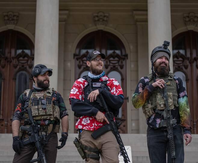 지난 17일(현지 시각) 미시간주 랜싱의 주의회 의사당 건물 앞에서 무장 민병대 소속 인사들이 총기를 들고 서 있다. /AFP 연합뉴스