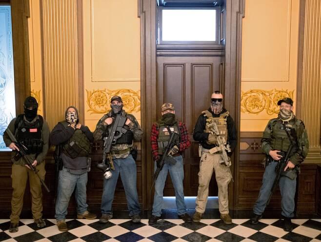 지난 4월 30일(현지 시각) 미시간주 랜싱의 주의회 의사당에서 무장 민병대 소속 인사들이 총기를 들고 서 있다. 이들은 민주당 소속 주지사가 코로나 확산 방지를 위한 봉쇄 조치를 연장하겠다고 하자, 이에 항의하기 위해 의사당을 점거했다. /AFP 연합뉴스