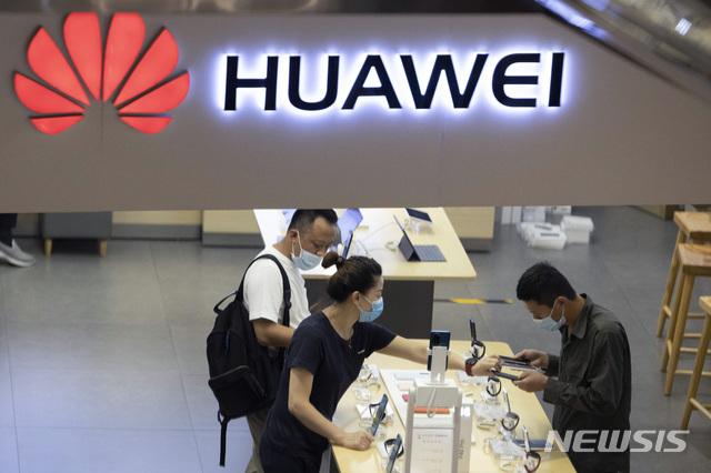 [베이징=AP/뉴시스] 7월15일(현지시간) 중국 베이징의 화웨이 매장에서 고객들이 신종 코로나바이러스 감염증(코로나19)을 우려해 마스크를 착용한 채 쇼핑 중인 모습. 2020.09.11.