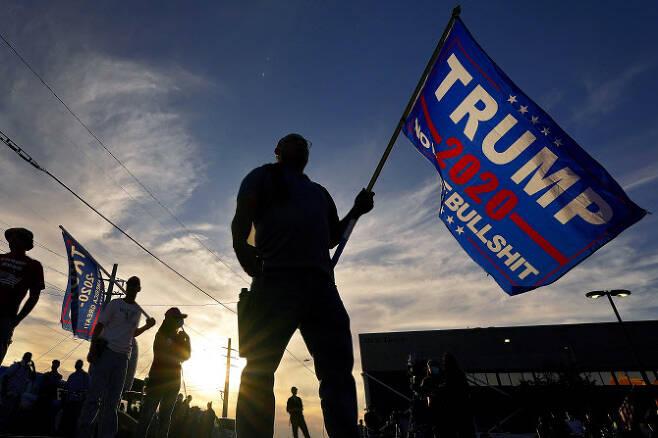지난 5일(현지시간) 미국 대선 개표작업이 사흘째 이어지는 애리조나주 피닉스의 매리코파 카운티 선거사무소 앞에 몰려든 도널드 트럼프 대통령 지지자들이 트럼프 지지 깃발을 들고 서 있다. (사진=AP/연합뉴스 제공)