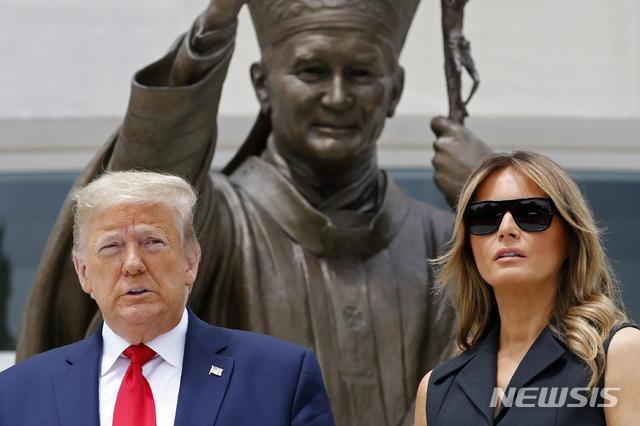 """[워싱턴=AP/뉴시스]도널드 트럼프 미국 대통령과 부인 멜라니아 여사가 2일(현지시간) 미 워싱턴DC 내 성 요한 바오로 2세 국가 성지를 방문해 동상 앞에 헌화 후 기념촬영을 하고 있다. 멜라니아 여사는 이날 기념촬영을 하면서 트럼프 대통령의 웃어달라는 요청에 불편한 기색을 보인 것으로 전해졌다. 웃으며 사진을 찍던 트럼프 대통령이 멜라니아에게 """"좀 웃지 그래?""""(Can you please smile?)라고 하자 멜라니아 여사는 억지로 웃는 표정을 짓고 이내 무뚝뚝한 모습으로 돌아왔으며 이 장면은 SNS를 통해 퍼지고 있다. 2020.06.03."""