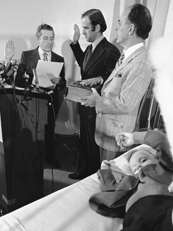 바이든 당선인이 교통사고로 아내와 딸을 잃은 직후인 1973년 1월 장남 보 바이든이 누워있는 병실에서 상원의원 선서를 하고 있다. [AP=연합뉴스]
