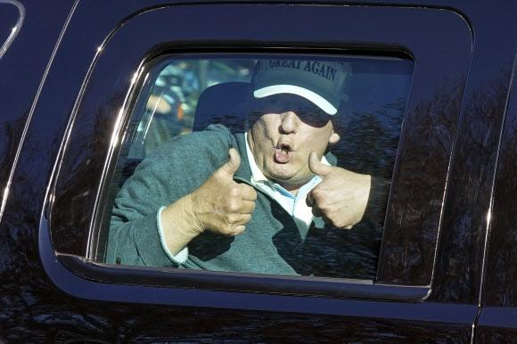 대선 패배를 인정하지 않고 있는 도널드 트럼프 미국 대통령이 8일(현지시간) 버지니아주 스털링에 있는 본인 소유 트럼프 내셔널 골프클럽에서 골프를 친 뒤 떠나면서 자신감을 보여 주려는 듯 엄지손가락을 들어 보이고 있다. 전날에 이어 이틀째 골프를 즐긴 그는 이날 차량 이동 중 골프장 주변에 모인 지지자와 항의 시위대를 지나쳤다.스털링 AP 연합뉴스