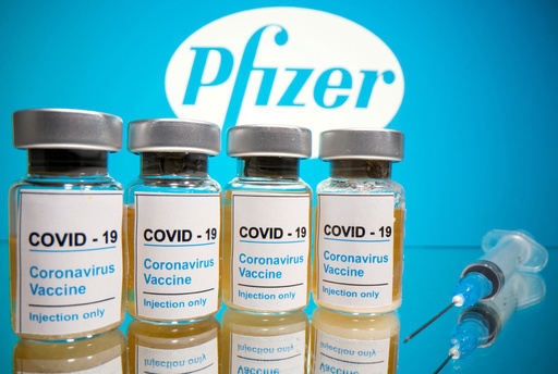 미국 제약사 화이자 로고를 배경으로 코로나19 백신이 담긴 유리병과 주사기가 놓여 있는 모습. 세계일보 자료사진