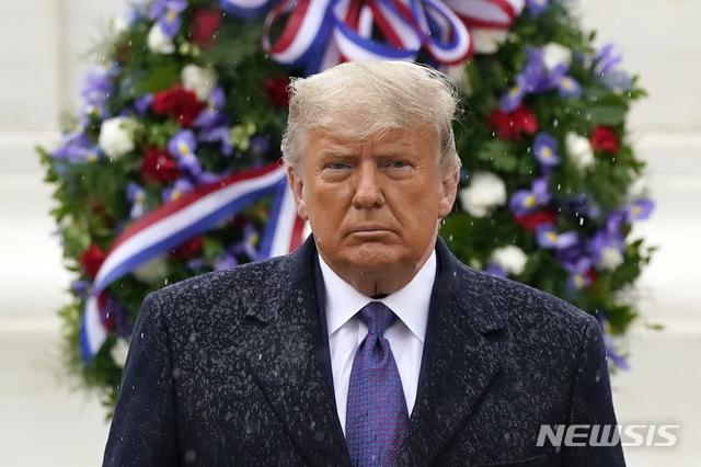 [알링턴=AP/뉴시스]도널드 트럼프 미국 대통령이 11일(현지시간) 재향군인의 날을 맞아 버지니아주 알링턴에 있는 알링턴 국립묘지를 찾아 무명용사비를 참배한 후 비를 맞으며 돌아서고 있다. 마스크를 쓰지 않고 행사에 참석한 트럼프 대통령은 아무런 발언도 하지 않았다. 2020.11.12.