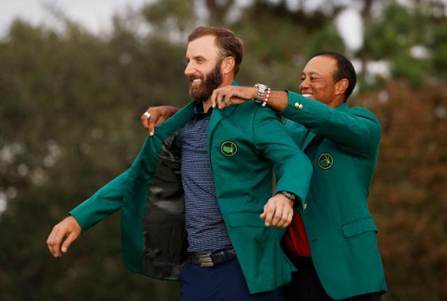 지난해 마스터스 토너먼트 우승자 타이거 우즈(오른쪽)가 16일 미국 조지아주 오거스타 내셔널 골프클럽에서 열린 제84회 마스터스 토너먼트에서 작올해 대회에서 우승한 더스틴 존슨에게 그린 재킷을 입혀주고 있다. 오거스타=로이터 연합뉴스