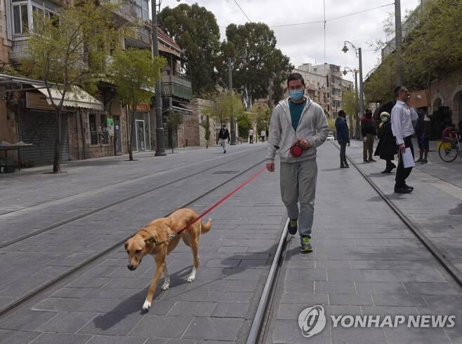 마스크를 착용한 한 시민이 개를 데리고 산책하고 있다.  [UPI=연합뉴스]