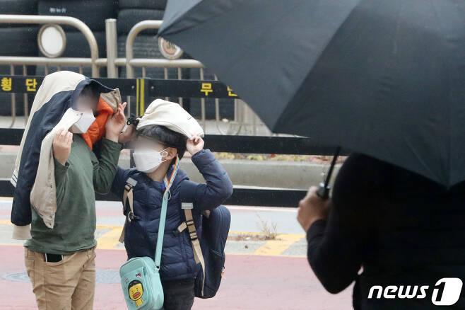 17일 오후 경기도 오산시내에서 초등학생들이 소나기가 내리자 옷과 가방을 머리에 쓴 채 비를 피하고 있다. 2020.11.17/뉴스1 © News1 조태형 기자
