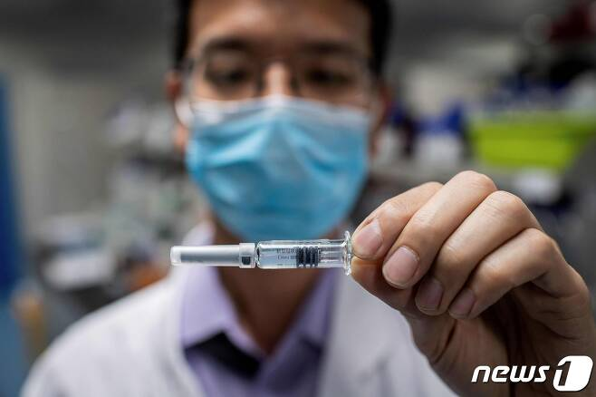 한 중국 의료진이 코로나19 백신 주사약을 들어보이고 있다. © AFP=뉴스1