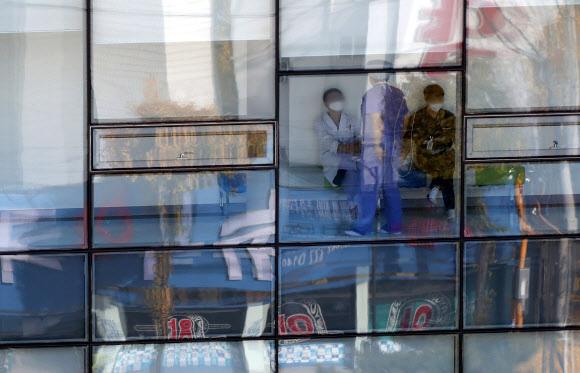 코호트 격리 들어간 전남대병원… 22일까지 외래·응급실 진료 중단17일 광주 동구 전남대병원에서 코로나19 확진자가 연이어 발생해 코흐트(동일 집단) 격리에 들어간 본원 1동 유리창 너머로 의료진이 보인다. 전남대병원은 이날 오전 9시부터 1동 3층부터 11동 병실을 격리했고 하루 4000여명 규모인 외래와 응급실 진료 중단도 오는 22일까지로 연장한다.광주 연합뉴스