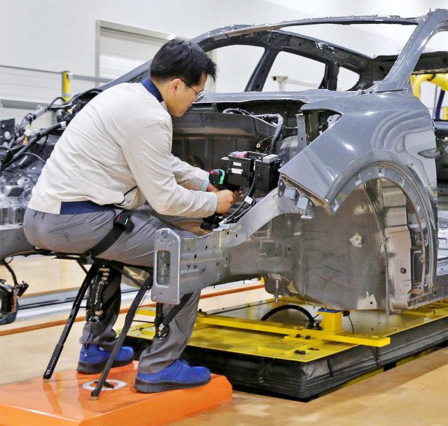 현대자동차 직원이 무릎을 앞으로 굽혀도 의자에 앉은 것처럼 편한 자세로 있을 수 있게 하는 웨어러블 로봇 'H-CEX'를 착용한 채 차량 조립 작업을 하고 있다. 현대차가 개발한 H-CEX와 같은 웨어러블 로봇은 산업 현장에서 제조 및 물류 과정에 널리 쓰이고 있다. 현대자동차그룹 제공