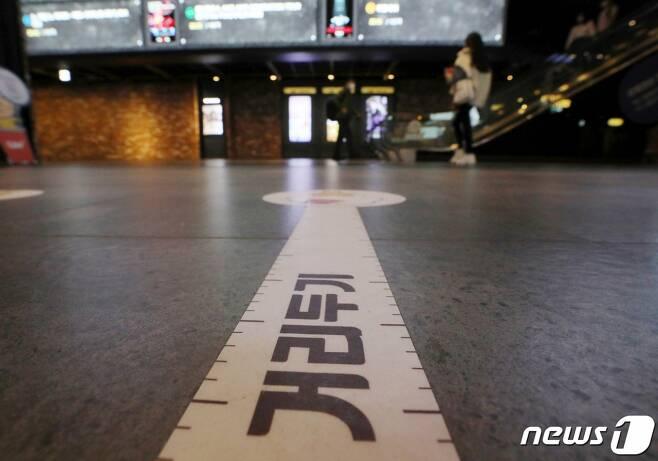 코로나19 확진자가 속출하며 거리두기 격상이 임박한 분위기다. 사진은 지난 18일 오후 서울 CGV용산에 거리두기 문구가 붙은 모습. /사진=뉴스1