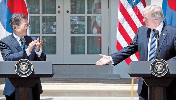 문재인 대통령이 2017년 6월 30일(현지시간) 백악관에서 공동 언론발표를 마친 뒤 박수를 치자 도널드 트럼프 미국 대통령이 악수를 청하고 있다. 김성룡 기자