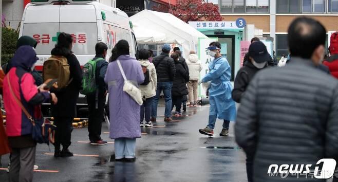 22일 오전 서울 중구 국립중앙의료원에 마련된 선별진료소에서 내원객들이 코로나19 검사를 위해 줄을 서서 대기하고 있다./사진제공=뉴스1