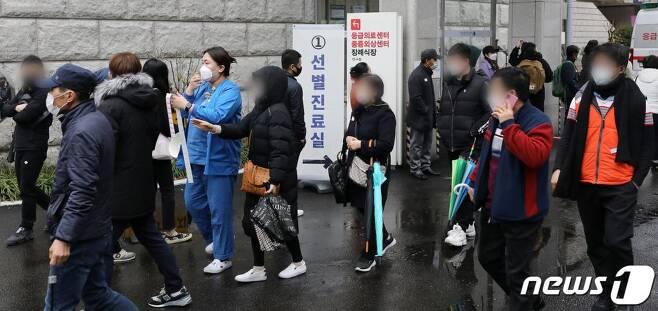 22일 오전 서울 중구 국립중앙의료원에 마련된 선별진료소에서 의료진이 내원객에게 코로나19 검체 채취를 위해 번호표를 배부하고 있다. /사진=뉴스1