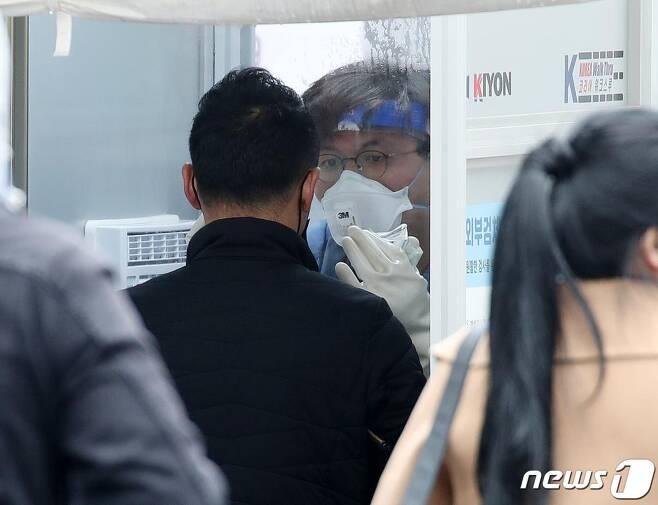 22일 오전 서울 중구 국립중앙의료원에 마련된 선별진료소에서 의료진들이 내원객에게 코로나19 검체 채취를 하고 있다. /사진=뉴스1