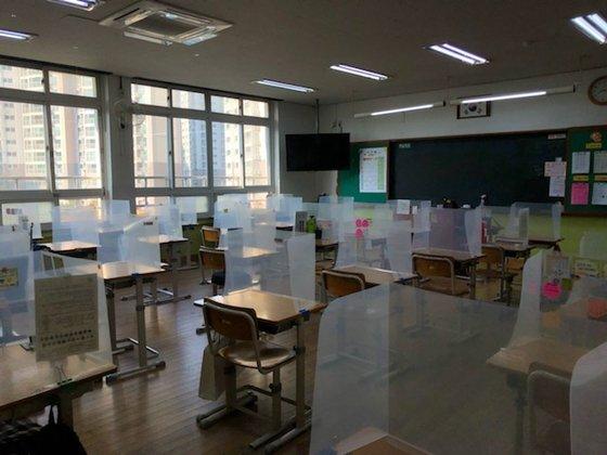 중학교 1학년 교실의 모습. 자리는 한줄씩 배치돼 있고 책상마다 투명 가림판이 설치돼 있다. [사진 류새봄 양]
