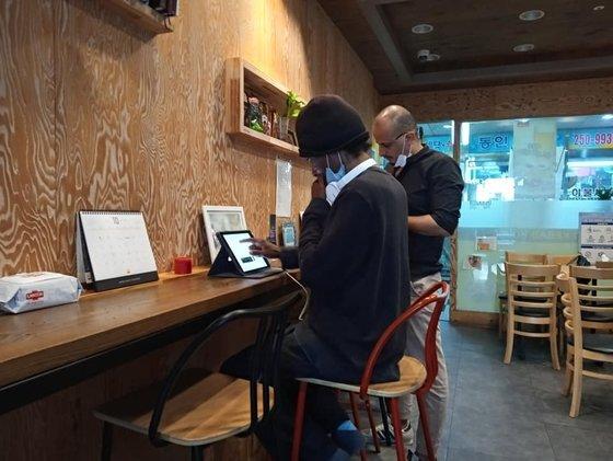 A(앞줄)씨는 한국에 들어온 뒤 자신이 겪은 일을 매일 개인 PC에 정리한다. 나중에 시로 풀어내기 위해서다. 홍주민 목사 제공