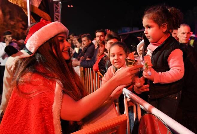 [다마스쿠스(시리아)=신화/뉴시스]산타클로스 복장을 한 여성이 22일(현지시간) 시리아 수도 다마스쿠스 서쪽 마제 고속도로에 세워진 크리스마스트리 근처에서 어린이들에게 사탕을 나눠주고 있다. 이날 크리스마스트리 주변에서 음악회가 열리고 산타클로스로 분장한 어른들이 어린이들에게 사탕을 나눠주는 행사가 열렸다. 2019.12.23.