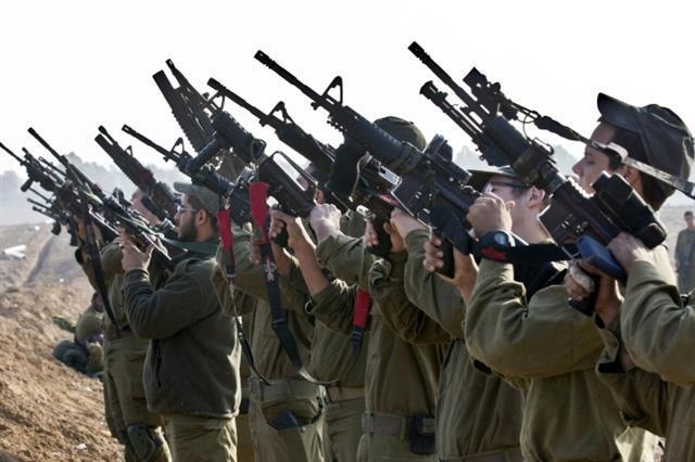 국경지역에서 이스라엘 기갑부대 대원들이 소총을 점검하는 모습.AFP 엽합뉴스