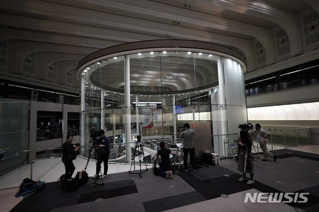 [도쿄=AP/뉴시스] 일본 도쿄증권거래소는 전산 시스템에 문제가 발생해 지난 10월 1일 하루 모든 종목의 거래를 정지한다고 발표했다. 사진은 이날 증시 관련 매체들이 불꺼진 도쿄증권거래소를 촬영하는 모습. 2020.10.1.