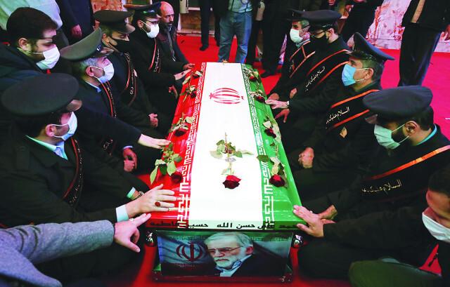 정복 차림의 이란군 고위 간부들이 30일(현지시간) 핵 과학자 모센 파흐리자데의 시신이 안치된 관에 손을 얹고 애도를 표하고 있다. 이란 핵개발에 참여한 것으로 알려진 파흐리자데는 3일 전 테헤란 외곽에서 테러 공격을 받아 숨졌다. EPA연합뉴스