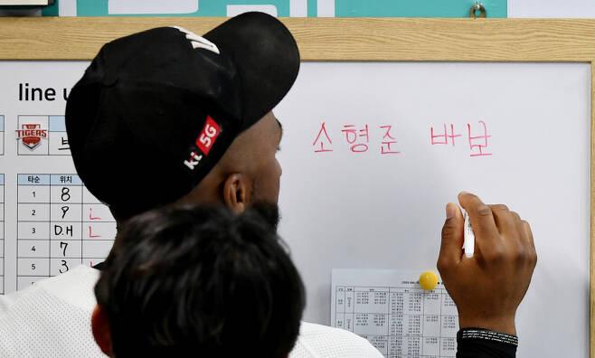 로하스가 덕아웃 벽에 걸린 화이트보드에 '소형준 바보'라는 문구를 쓰며 한글 공부를 하고 있다. 수원=정재근 기자