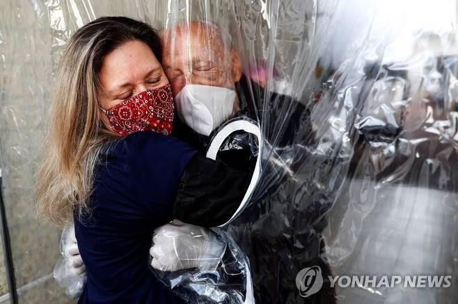 '코로나19 허그 커튼' 포옹하는 브라질 부녀 [EPA=연합뉴스 자료사진]