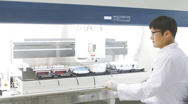 국내 주요 기업이 코로나19 치료제와 백신을 내놓기 위해 연구에 한창이다. 사진은 약 개발을 위해 실험을 하는 셀트리온 연구원.  <셀트리온 제공>