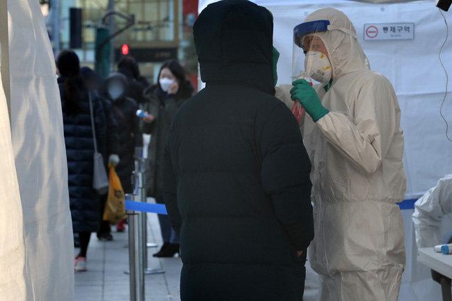 12월 14일 오후 서울 종로구 탑골공원 앞에 마련된 코로나19 임시 선별진료소를 찾은 시민이 코로나19 검사를 받고 있다.  [뉴스1]