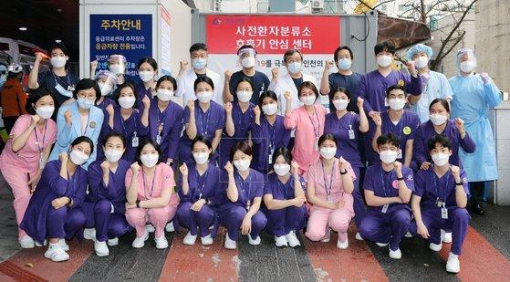박정은 간호사(첫번째 줄 왼쪽에서 다섯번째)를 비롯한 가천대 길병원 응급실 간호사들이 사전환자 분류소 앞에 모여서 기념사진을 찍고 있다. [가천대길병원]