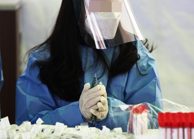 17일 서울역 광장에 마련된 중구 임시 선별검사소에서 의료진이 핫팩으로 추위를 견디고 있다. 연합뉴스