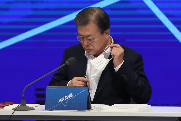 문재인 대통령이 17일 서울 중구 대한상공회의소에서 열린 2021년 경제정책방향 보고회에서 발언에 앞서 마스크를 벗고 있다. 연합뉴스