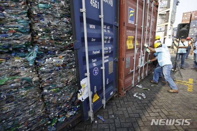 [자카르타=AP/뉴시스] 지난해 9월18일(현지시간) 인도네시아 자카르타의 탄중페락 항구에서 작업자들이 플라스틱 쓰레기로 가득한 컨테이너를 잠그고 있다.  인도네시아 정부는 폐플라스틱과 유해 물질이 들어찬 컨테이너 수백 개를 서구 국가들에 반송하고 있다. 중국이 지난해 폐플라스틱 수입을 중단하면서 선진국들이 동남아 국가로 폐기물을 수출하면서 필리핀과 인도네시아, 말레이시아 등이 골머리를 앓고 있다. 2019.09.18.