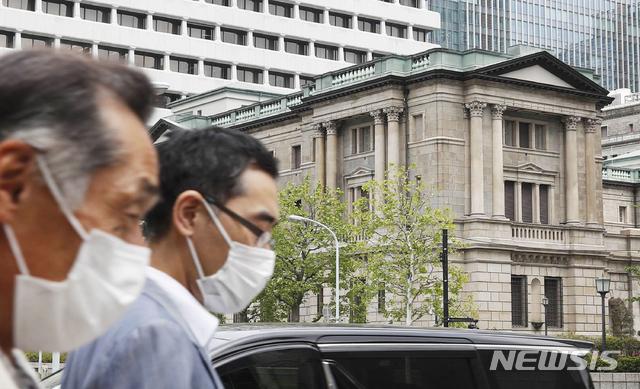 [도쿄=AP/뉴시스]지난 4월 27일 일본 도쿄에 위치한 일본은행 앞으로 마스크를 쓴 시민들이 걸어가고 있다.  2020.04.27.