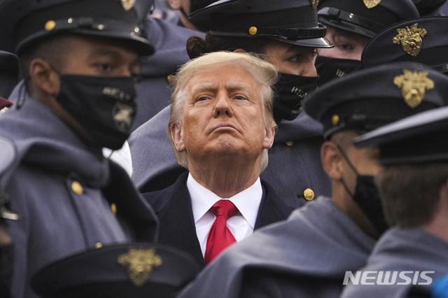 [웨스트포인트(미 뉴욕주)=AP/뉴시스]마스크를 쓴 육사 생도들 사이에서 혼자만 마스크를 쓰지 않은 도널드 트럼프 미 대통령이 지난 12일 뉴욕주 웨스트포인트의 미치 스타디움에서 열린 미 육사와 해사 간 미식축구 경기를 지켜보고 있다. 그는 19일(현지시간) 어떤 증거도 제시하지 않은 채 미국에 대한 사이버 공격의 배후는 러시아가 아니라 중국이며 러시아의 영향은 별것 아니라고 주장해 마이크 폼페이오 국무장관 및 다른 고위 관리들의 주장을 반박했다. 2020.12.20