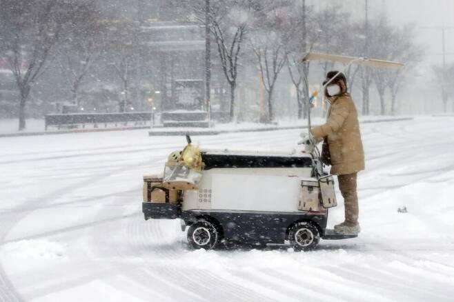 대설주의보가 내려진 지난 12월30일 오전 광주 서구 상무지구에서 한국야쿠르트 프레시매니저가 눈길로 변한 도로를 지나고 있다. 연합뉴스