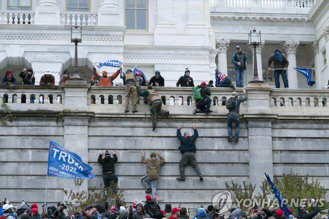 미 의회의사당 외벽 기어오르는 트럼프 지지자들[AP=연합뉴스]