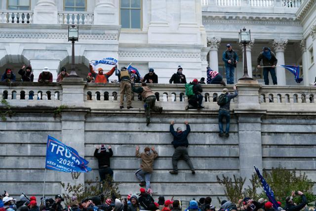 도널드 트럼프 미국 대통령 지지 시위대가 6일 워싱턴 국회의사당 서쪽 벽을 기어오르고 있다. 워싱턴=AP 연합뉴스