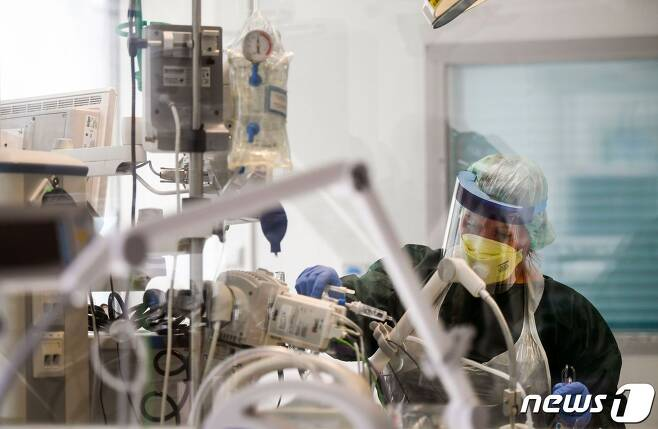 지난해 4월1일 독일 노르트라인베스트팔렌주 에센의 대학병원 격리병동에서 간호사가 코로나19 환자를 돌보고 있다. © AFP=뉴스1