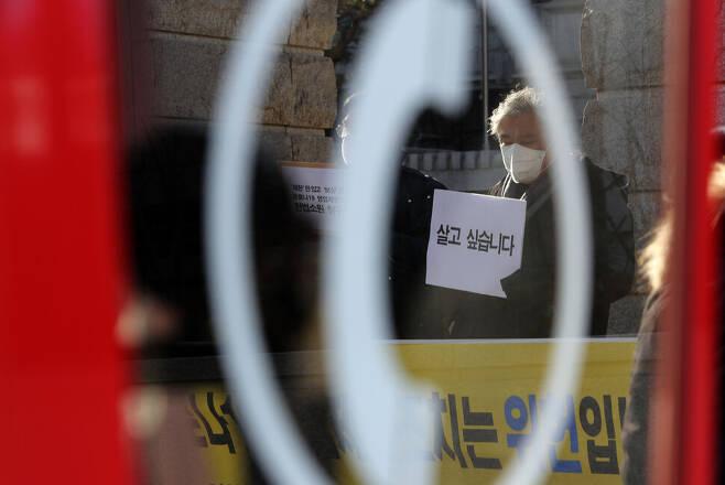 시민단체와 호프집·피시(PC)방 등 업주들이 5일 오후 서울 종로구 재동 헌법재판소 앞에서 제한만 있고 보상은 없는 코로나19 영업 제한조치는 위헌이라며 헌법소원을 청구하는 기자회견을 열고 있다. 공중전화 박스 너머로 '살고 싶습니다'라고 적힌 손팻말을 든 참가자가 보이고 있다. 이종근 선임기자 root2@hani.co.kr