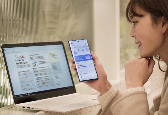 이동통신사 직원이 13일 패스(PASS) 인증서를 이용해 국세청 연말정산 서비스에 접속하는 시범을 보이고 있다.15일부터 패스인증서를 이용하는 고객은 국세청 홈택스 사이트에서 '간편인증 로그인'을 선택한뒤 '패스인증서'를 골라 간편하게 접속할 수 있다.
