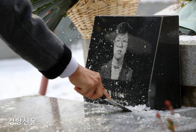 박종철 열사 사망 34주기인 14일 오후 경기 남양주시 마석 모란공원 민족민주열사 묘지에서 열사의 유가족들이 묘에 언 얼음을 정리하고 있다. 열사와 열사의 아버지 고 박정기씨의 묘에는 미처 녹지 못한 눈이 쌓여 있었다. / 권도현 기자