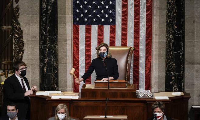 도널드 트럼프 미국 대통령에 대한 탄핵소추안 표결을 진행하는 낸시 펠로시 하원의장이 13일(현지시간) 하원 본회의장 내 의장석에서 의사봉을 두드리고 있다. 워싱턴=AP연합뉴스