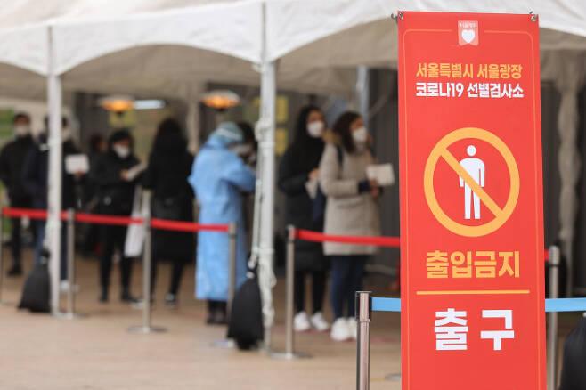 코로나19 확진자가 나흘째 500명대를 기록한 15일 서울시청 앞 마련된 임시선별진료소에서 시민들이 검사를 받기 위해 줄을 서 있다. 연합뉴스.