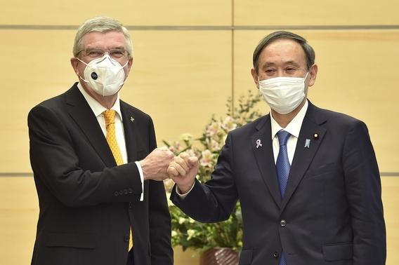 바흐 IOC 위원장과 '주먹 인사' 나누는 스가 일본 총리. /AP·연합뉴스