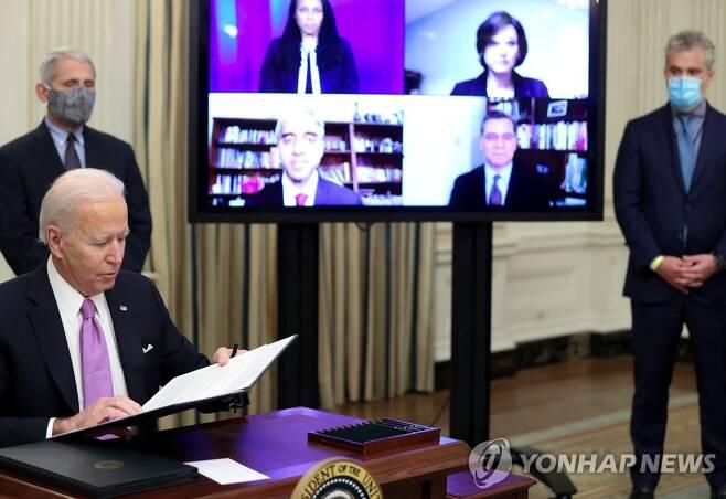 코로나19 행정명령에 서명하는 바이든 미국 대통령 (워싱턴 로이터=연합뉴스) 조 바이든 미국 대통령이 21일(현지시간) 백악관에서 앤서니 파우치 국립알레르기·전염병연구소 소장(왼쪽)이 지켜보는 가운데 코로나19 대응에 관한 행정명령에 서명하고 있다. jsmoon@yna.co.kr