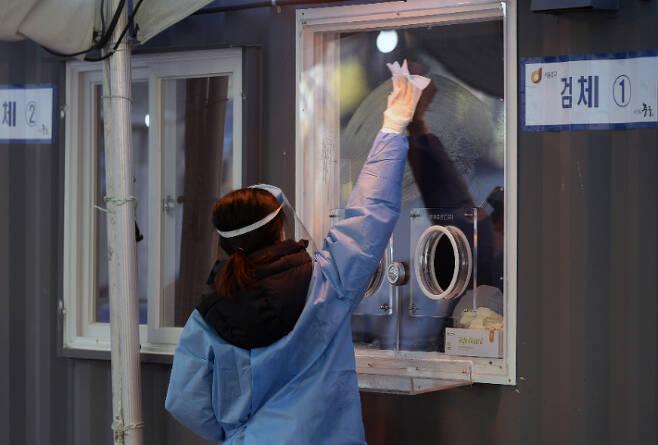 임시 선별진료소에서 의료진이 검체소를 소독하고 있다. 이한형 기자
