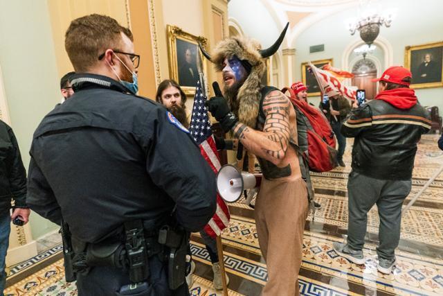 6일 미국 워싱턴 연방의회 의사당 난입 사태 당시 뿔 달린 털모자를 쓰고 얼굴에 페인트를 칠한 채 폭동에 가담한 극우 음모론 단체 '큐어넌' 회원 제이컵 앤서니 챈슬리가 상원 본회의장 밖에서 의회 경위들과 대치하고 있다. 워싱턴=AP 연합뉴스