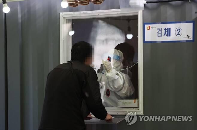사진=서울역광장에 설치된 임시선별진료소에서 의료진이 검체를 채취하고 있다. 연합뉴스